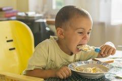 Chłopiec 2 roku je owsiankę Children& x27; s stół Pojęcie child& x27; s niezależność szczęśliwy chłopiec łasowanie obraz royalty free
