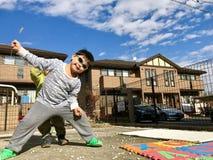 Chłopiec Rozciąga ręki I nogi przy podwórkem z niebieskiego nieba tłem zdjęcie royalty free
