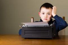 Chłopiec rozpraszająca uwagę przed starym maszyna do pisania fotografia stock