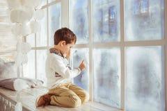 Chłopiec rysuje na zamarzniętym okno w zimie Zdjęcie Royalty Free