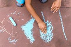 Chłopiec rysunek z barwioną kredą na ceglanej podłoga w lato czasie fotografia royalty free