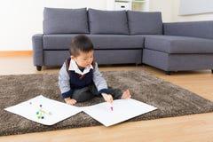 Chłopiec rysunku miejsca siedzące na dywanie i obrazek obrazy stock