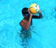 Chłopiec rzuca piłkę w pływackiej piłce fotografia royalty free