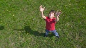 Chłopiec rzuca up piłkę, stoi na zielonym gazonie zbiory
