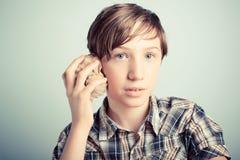 Chłopiec słucha dźwięk morze fotografia stock