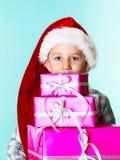 Chłopiec Santa pomagiera kapelusz z różowymi prezentów pudełkami Fotografia Royalty Free