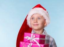 Chłopiec Santa pomagiera kapelusz z różowymi prezentów pudełkami Zdjęcie Stock
