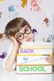 Chłopiec siedem lat z książkami tylna szkoły fotografia stock