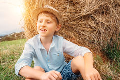 Chłopiec siedzi blisko dużego haystack na polu Obraz Royalty Free
