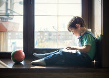 Chłopiec siedzi blisko okno i używa pastylkę Obraz Stock