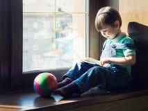Chłopiec siedzi blisko okno i używa pastylkę Zdjęcia Stock
