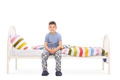 Chłopiec siedzi na łóżku w błękitnych piżamach Fotografia Royalty Free