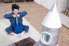 Chłopiec siedzi na dywanie i wszczyna rakietę w piżamach Obraz Royalty Free