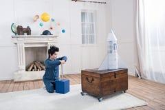Chłopiec siedzi na dywanie i wszczyna zabawki rakietę w piżamach Zdjęcia Stock