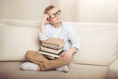 Chłopiec siedzi na kanapie z stosem książki i patrzeje daleko od w eyeglasses Obraz Royalty Free