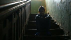 Chłopiec siedzi na krokach zaniechany ganeczek Pojęcie dziecka ` s narkomania, cygaństwo, bezdomność zdjęcie wideo