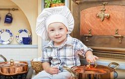Chłopiec siedzi na kuchennym stole obrazy royalty free