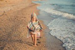 Chłopiec siedzi na plaży w pasiastej koszula z morski lifebuoy, liferound Chłopiec siedzi na piasku na pięknej plaży Beautif fotografia stock