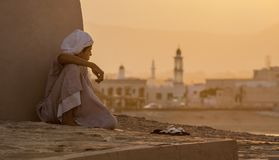 Chłopiec siedzi obok ściennego dopatrywania zmierzch Zdjęcie Stock