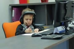 Chłopiec siedzi przy komputerem w biurze z hełmofonami i robi notatkom Zdjęcie Stock