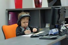 Chłopiec siedzi przy komputerem w biurze z hełmofonami i robi notatkom Zdjęcia Stock