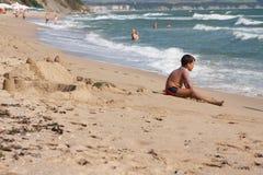 Chłopiec siedzi przy sztukami z jego rękami i plażą obraz stock