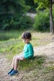 Chłopiec siedzi w lasowej haliźnie obrazy stock