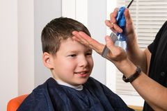 Chłopiec siedzi w piękno salonie fryzjer zwilża włosy dla fryzury obraz stock