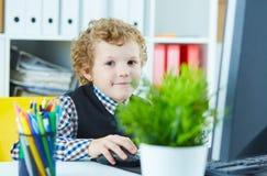 Chłopiec siedzi za pracującym komputerem w biurowych spojrzeniach w kamerę i ono uśmiecha się Obrazy Royalty Free
