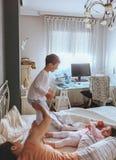 Chłopiec skacze nad łóżkiem z jego rodziną Fotografia Stock
