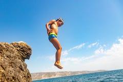 Chłopiec skacze od falezy w morze na gorącym letnim dniu Wakacje na plaży Pojęcie aktywna turystyka zdjęcia royalty free