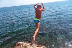 Chłopiec skacze od falezy w morze na gorącym letnim dniu Wakacje na plaży Pojęcie aktywna turystyka zdjęcie stock