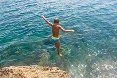 Chłopiec skacze od falezy w morze na gorącym letnim dniu Wakacje na plaży Pojęcie aktywna turystyka fotografia stock