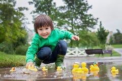 Chłopiec, skacze w błotnistych kałużach w parku, guma nurkuje i zdjęcie stock