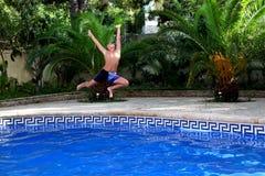 Chłopiec skacze w pływackiego basen zdjęcia royalty free