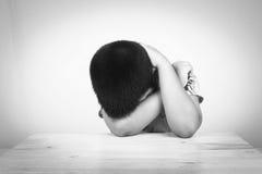 Chłopiec smutny być usytuowanym samotnie przy drewnianym stołem zdjęcia stock