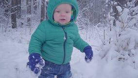 Chłopiec spacery i bawić się na śnieżnym drewnie, dziecka odprowadzenie na zima lasu zwolnionym tempie zbiory wideo