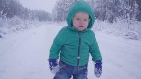 Chłopiec spacery i bawić się na śnieżnym drewnie, dziecka odprowadzenie na zima lasu zwolnionym tempie zdjęcie wideo