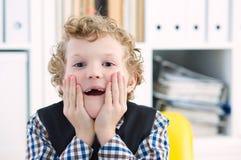 Chłopiec spojrzenia przy kamerą z niespodzianką, stawia jego ręki Obrazy Royalty Free