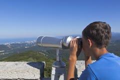 Chłopiec spojrzenia przy Sochi przez lornetek od wierza na halnym Dużym Ahun Obraz Stock