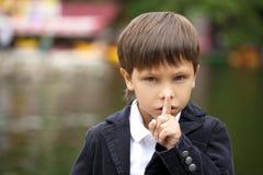 Chłopiec stawiał forefinger wargi jak znaka cisza obrazy stock