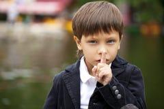 Chłopiec stawiał forefinger wargi jak znaka cisza zdjęcie stock
