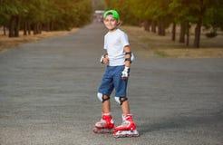 Chłopiec stawiająca na ochronnych kolanowych ochraniaczach i łyżwach w parku zdjęcie stock