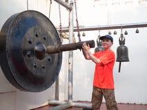 Chłopiec strajki i ono uśmiecha się gong obrazy stock