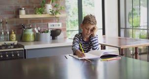 Chłopiec studiowanie przy stołem w kuchni 4k w domu zdjęcie wideo