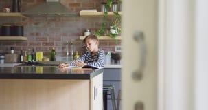 Chłopiec studiowanie przy stołem w kuchni 4k w domu zbiory