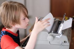 Chłopiec studiuje elektryczną maszynę do pisania obraz stock