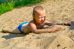 Chłopiec sunbathes na piasku obraz stock