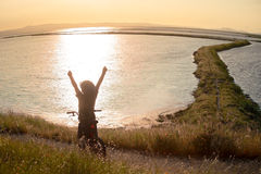 Chłopiec sylwetka z otwartymi rękami na rowerze przy zmierzchem Fotografia Stock
