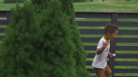 Chłopiec syn bawić się kryjówkę przy ogrodową jest ubranym koszulką i skrótami aport - i - wartości rodzinne grżą koloru lata sce zdjęcie wideo